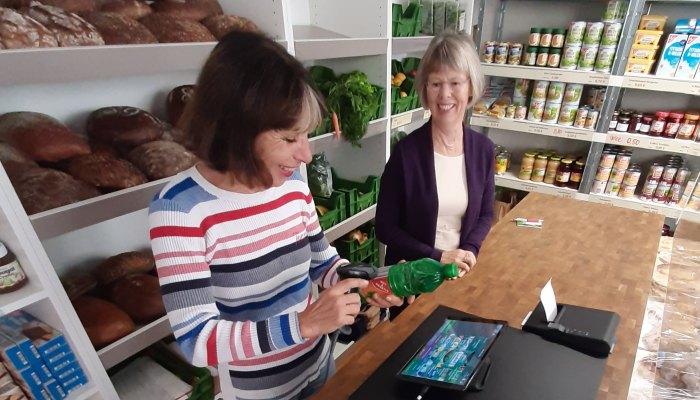 Zwei ältere Frauen in einem Lebensmittelladen, eine scannt eine Flasche ab, Kasse Speedy auf dem Tisch