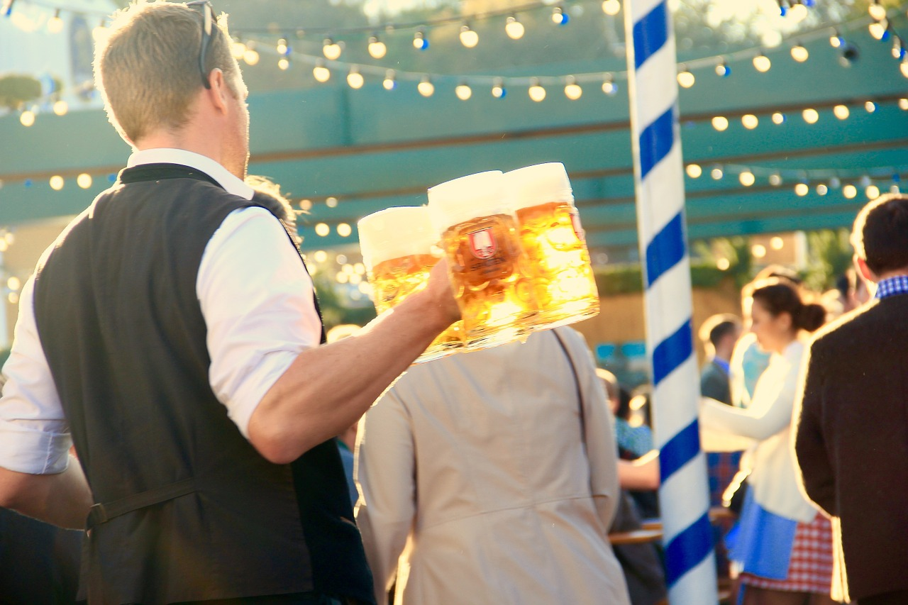 Kellner mit mehreren Maß Bier in den Händen