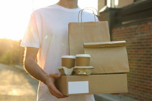 Lieferbote trägt braunen Karton, Tüten und Becher