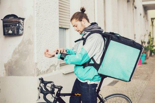 Lieferbote auf einem Fahrrad mit einem Waren-Rucksack - er schaut auf sein Smartphone, welches er am linken Unterarm trägt