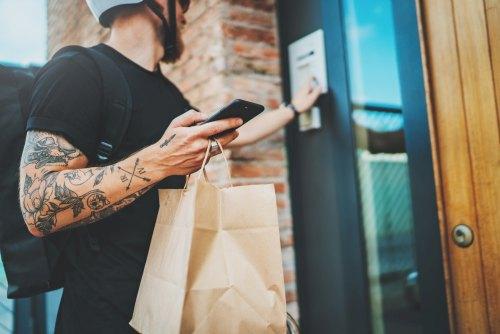 Lieferbote mit einem Radhelm und Waren-Rucksack - er klingelt an der Haustüre, sein Smartphone hält er in der anderen Hand