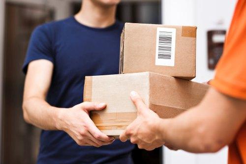 Lieferbote übergibt zwei braune Kartons