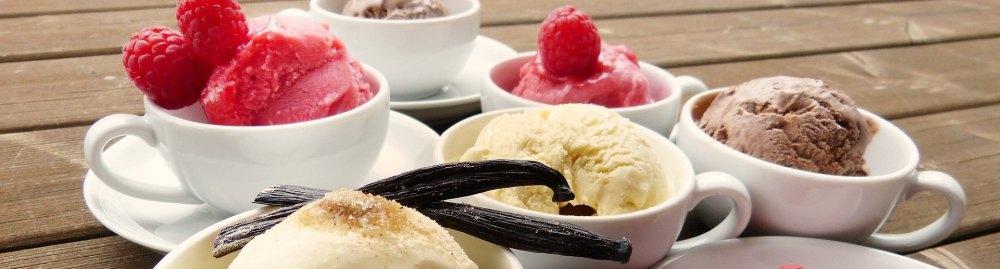 weiße Tassen gefüllt mit Eis: Vanille, Schoko und Himbeere - mit Früchten