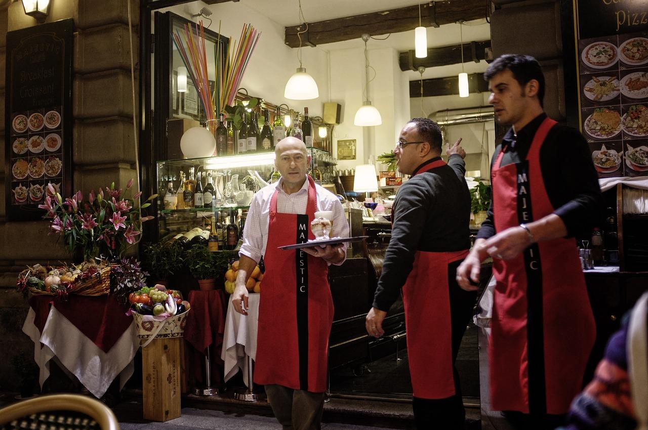 Drei männliche Kellner bei der Arbeit in einer (Straßen)Pizzeria