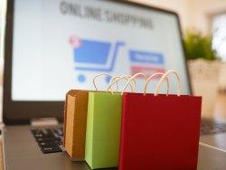 """Laptop mit unscharfem Schriftzug """"Online Shopping"""" und drei kleinen bunten Einkaufstaschen auf der Tastatur"""
