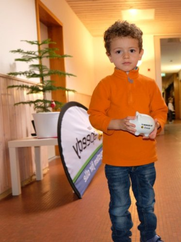 Junge im Kindergarten mit Speedy-Sparschwein in der Hand