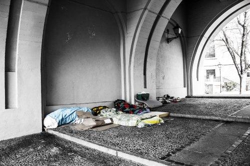 Matratzen und Decken auf dem Boden in einem überdachten Durchgang