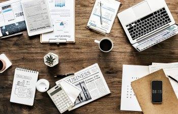 Arbeitsplatz, voll mit Papieren, Notizen, PC, Berechnungen etc.